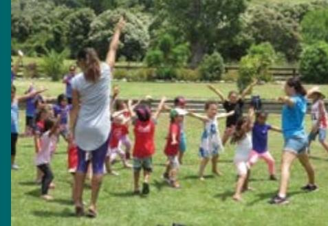 Two teachers and a group of 10 children do exercises outdoors on the grass.