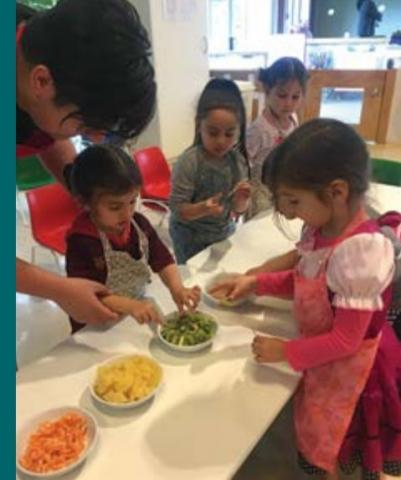 A teacher helps two students wearing aprons to take fruits from bowls on a table